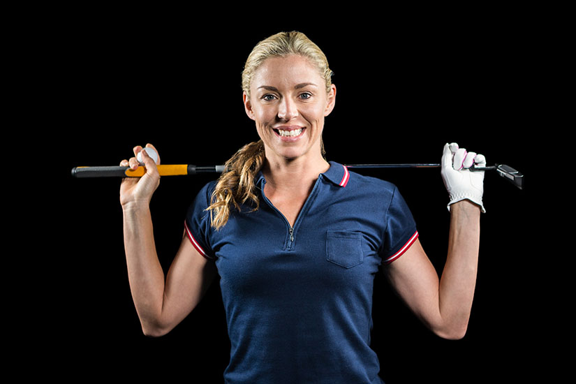 Portrait of golf player holding a golf club on black background